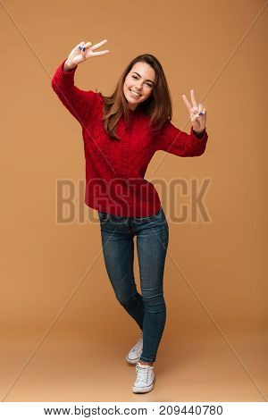 Full length portrait of young funny girl in casual wear showing peace gesture with two hands, looking at camera, isolated on beige background