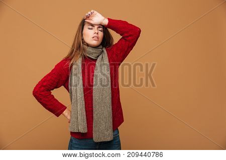 Close-up photo of ill young woman in warm casual wear touching her forehead with closed eyes, measuring temperature,  isolated on beige background