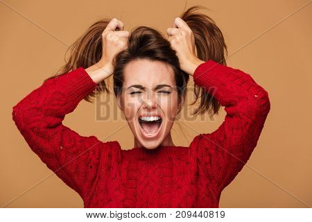 Photo of screaming brunette woman with closed eyes making two ponytails hairstyle, isolated on beige background