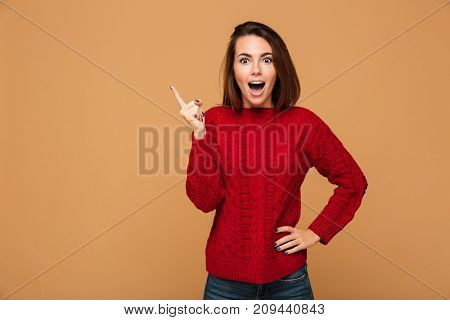 Happy young woman with opened mouth pointing with finger up, looking at camera, isolated on beige background