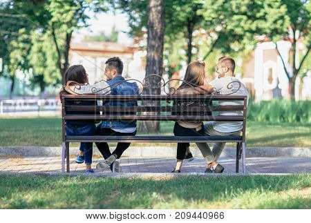 Two Lovers Couples Sitting On Different Ends Of One Bench
