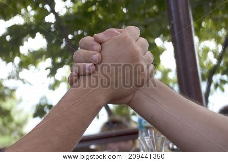 Arm Wrestling. Two people Arm wrestling on the outdoors
