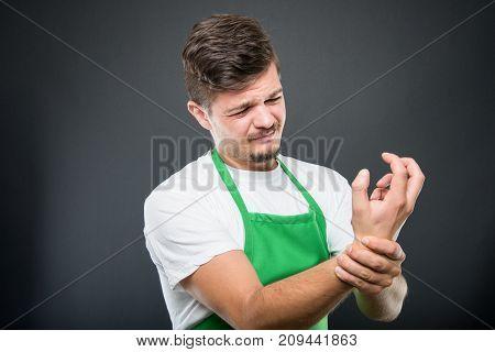 Portrait Of Supermarket Employer Holding Wrist Like Hurting