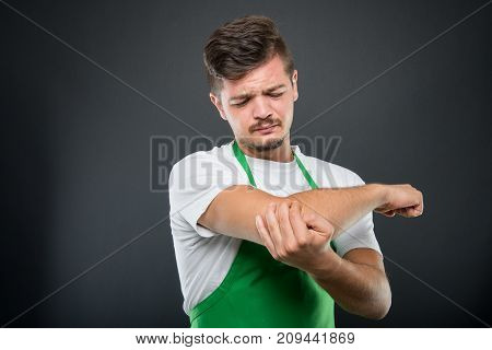 Portrait Of Supermarket Employer Holding Elbow Like Hurting