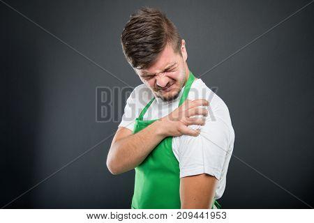 Portrait Of Supermarket Employer Holding Shoulder Like In Pain
