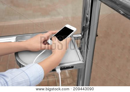 Young woman charging mobile phone, outdoors