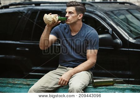 Man drinking alcohol near car