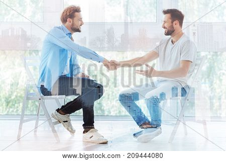 Problems solved. Positive young bearded man shaking hands with professional psychiatrist while expressing gratitude for helping