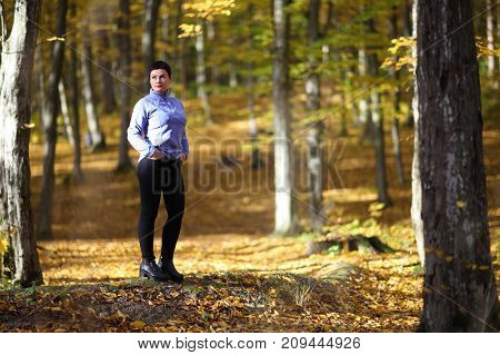 A beautiful mature woman is basking in the rays of the autumn sun in a clearing in the forest. Nice mature woman stands on a background of yellow autumn. Mature woman of the autumn forest.