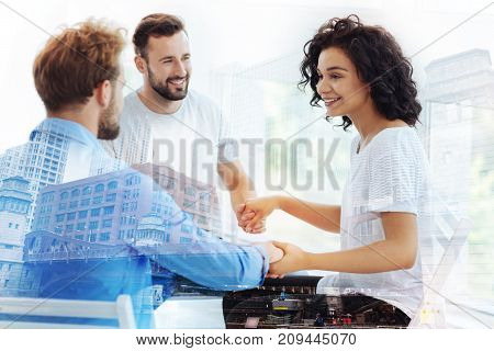 Calm minds. Group of cheerful friends having psychological session while holding hands and expressing delight