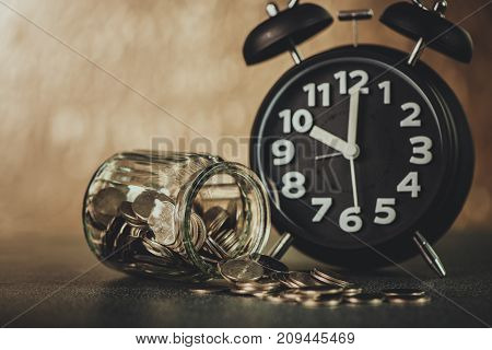 Alarm Clock And Step Of Coins Stacks With Coin In Glass Jar On Working Table, Time For Savings Money