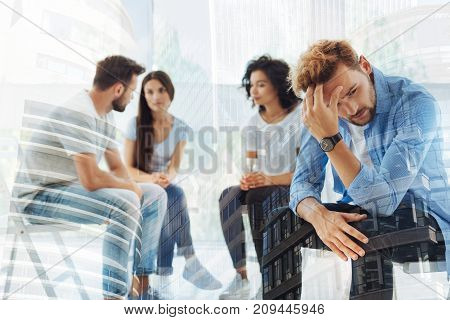 Unsuccessful relationships. Young bearded man touching his head while feeling frustrated and displeased