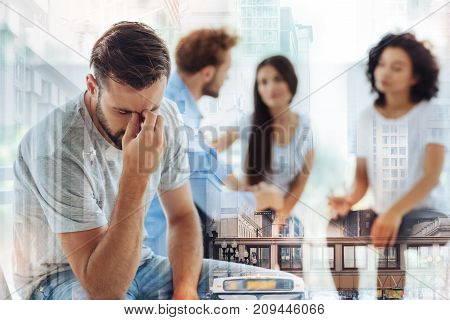 Drown in depression. Waist up of upset young man touching his face and being frustrated while waiting for psychologists advice