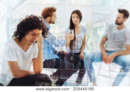Moral trauma. Waist up of frustrated young woman having bad mood while sitting and touching her face in psychologists office