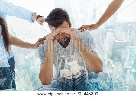 Giving support. Waist up of nervous man covering his head with hands while his colleagues providing moral help