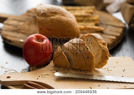 French Bread Baguette Cut On Wooden Board With Knife. With A Chocolate Butter And Red Apple.