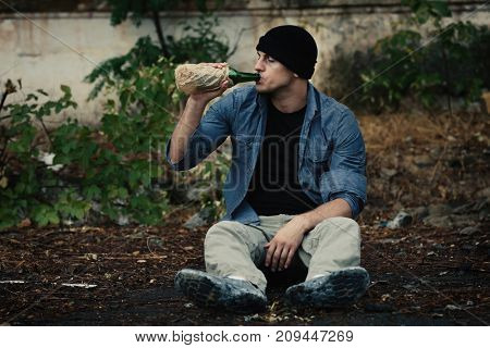 Man sitting on ground and drinking alcohol outdoors