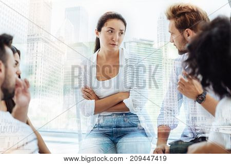 No way. Waist up of sceptical young woman keeping arms in crossed position expressing hesitation while having a talk with psychologist