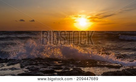 Landscape: Sea waves break against the rocks at sunset. Cyprus.
