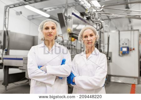 manufacture, industry and people concept - happy women technologists at ice cream factory shop