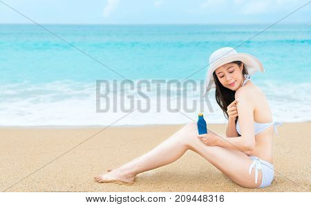 Woman Travel In Beach And Holding Sunscreen Bottle