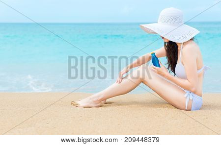 Girl Sitting On Beach And Using Sun Protection Oil