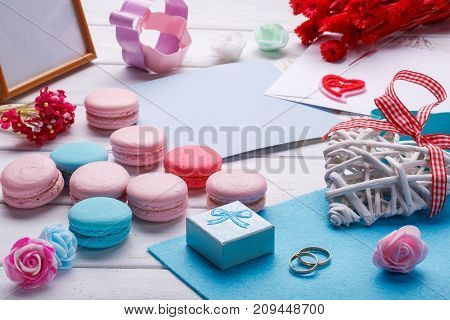 Colorful macaroons. Wedding subject. wedding rings. postcard with envelope over white wooden background