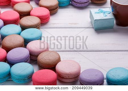 Valentine's day background with colorful macaroons and ring box over white wooden background. Place or space for text