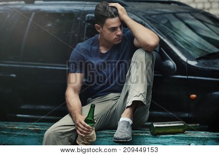 Man sitting with bottle of alcohol near car