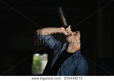 Man drinking alcohol in abandoned building
