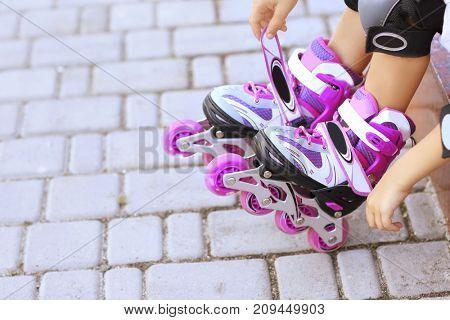 Legs of little roller skater, outdoors