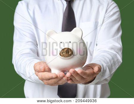 Young man with piggy bank, closeup