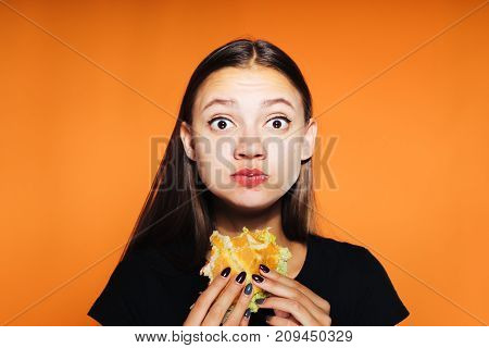 sexy girl eating an appetizing hamburger in her hands. tasty food, isolated on orange background