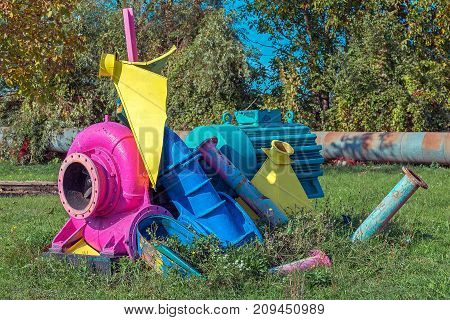 Remnants of industrial machinery painted in bright colors and placed in nature.