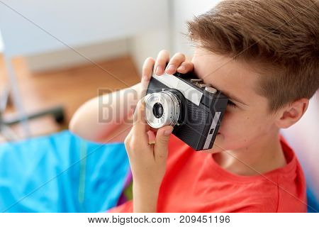 hobby, technology and people concept - close up of happy boy with film camera photographing at home
