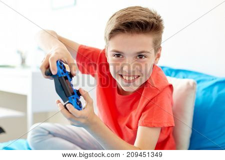 gaming, technology and people concept - smiling boy with gamepad playing video game at home poster