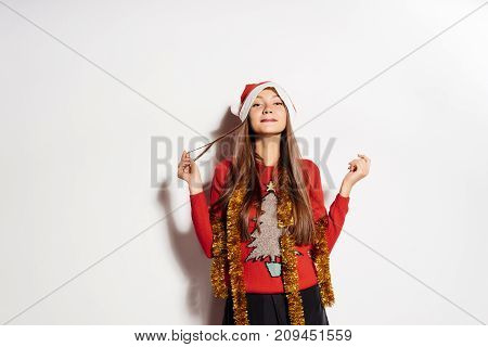 New Year, New Year's mood, decoration, a girl in a New Year's sweater and a Santa Claus hat, a merry Christmas