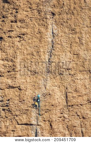 Long shot of many male climbers in a cliff