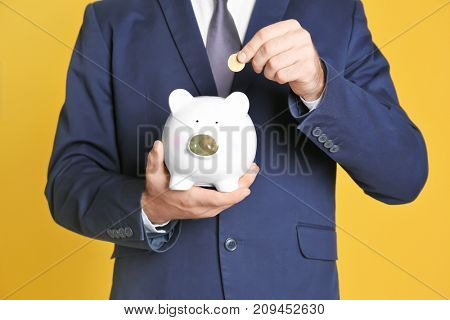 Young man putting coin into piggy bank on color background