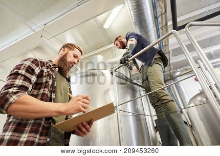 production, business and people concept - men with clipboard working at brewery or non-alcoholic beer plant