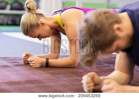 fitness, sport, exercising, training and people  concept - woman and man doing plank exercise in gym