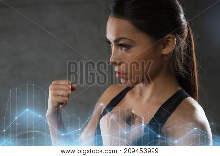 sport, fitness, martial arts and people concept - woman holding fists and fighting in gym