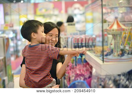 Young Asian Mother And Her Kid Shopping Toy In Shopping Mall