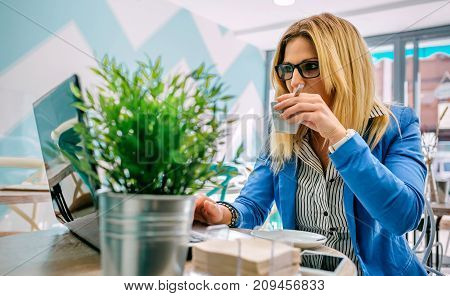 Woman drinking coffee and working with the laptop in a coffee shop