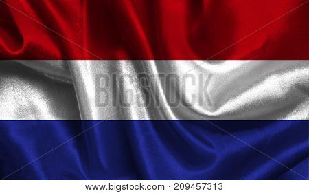 Realistic flag of Netherlands on the wavy surface of fabric. This flag can be used in design.