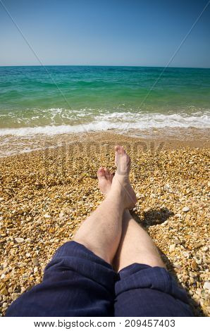 male feet on a beach against the sea