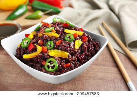 Dish with red rice on table