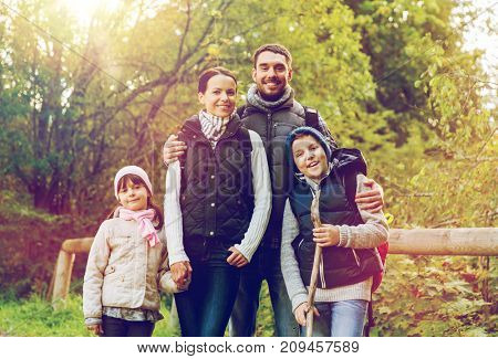 hike, travel, tourism and people concept - happy family walking with backpacks in woods