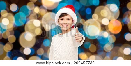 holidays, gesture, childhood and people concept - smiling happy boy in santa hat showing thumbs up over christmas lights background