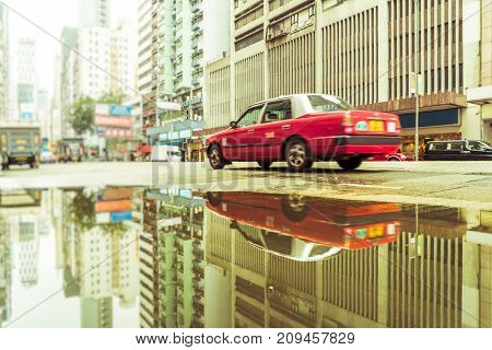 motion taxi reflecting at puddle,hong kong,china,asia.